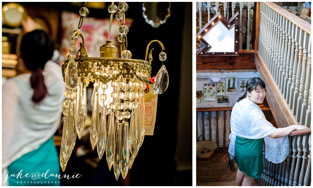 Dannie looks at goods on a shelf behind a chandelier, and she goes down the stairs to the lower level of the Paris Cafe