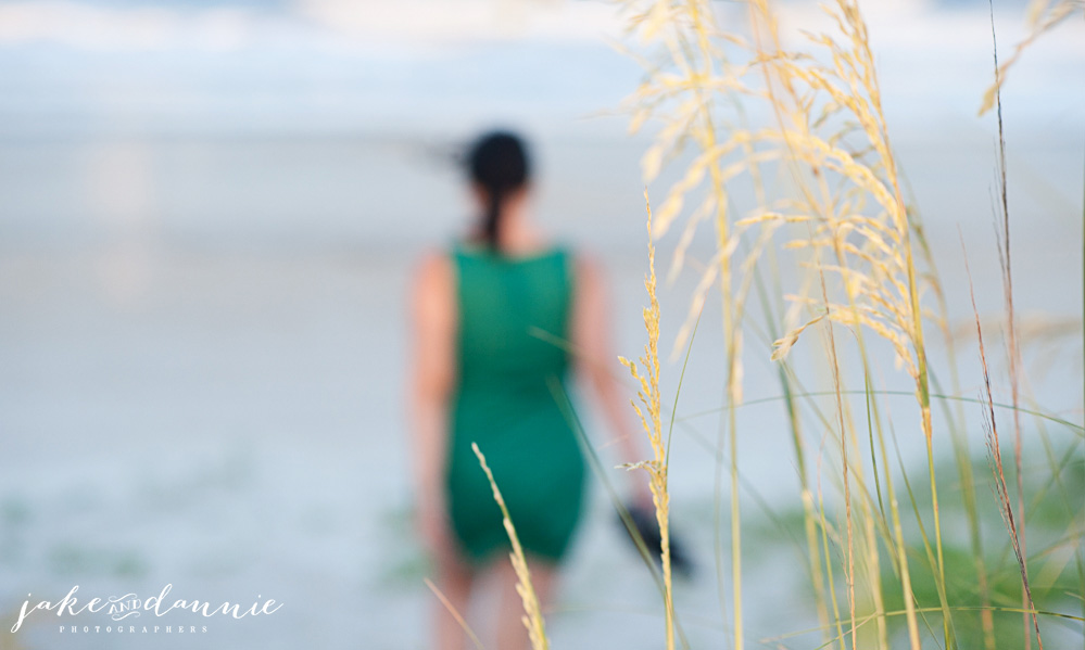A photo of the grass by the beach with Dannie walking toward the ocean in the background