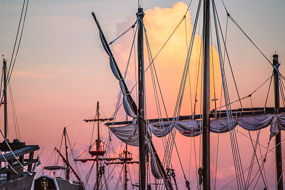 The masts of the tourist pirate ships with a beautiful cloud in the background at sunset