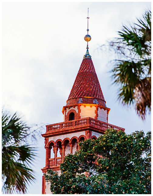 The bell tower at Flagler College poking up past the palm trees of St. Augustine, Florida